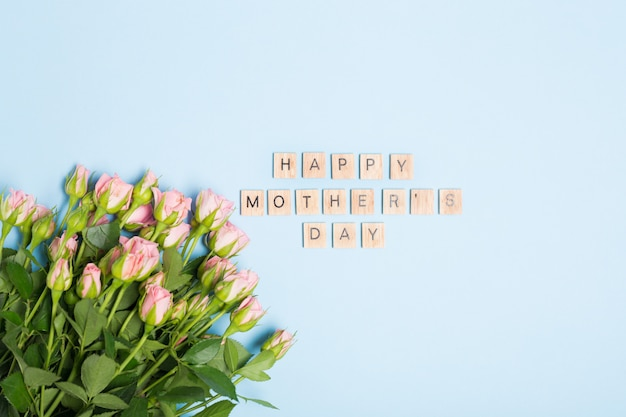 Szczęśliwy dzień matki tekst i różowe róże na niebieskim tle. wolna przestrzeń. leżał płasko. widok z góry.