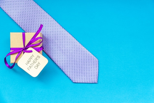Szczęśliwy dzień ojca napis z krawatem i pudełko na niebieskim tle. pozdrowienia i prezenty