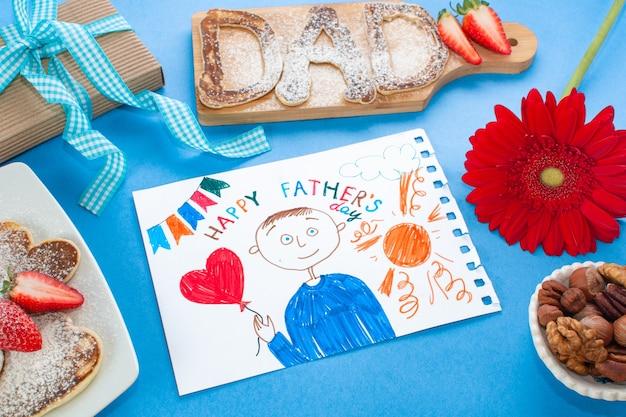 Szczęśliwy dzień ojca rysunek z prezentem, kwiatem, ciastem i naleśnikami na niebieskim tle