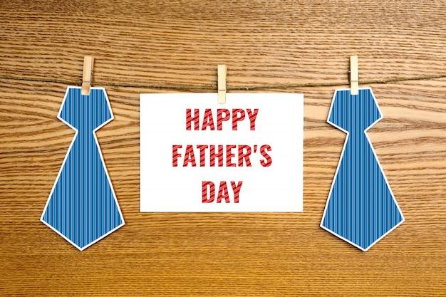 Szczęśliwy dzień ojca tekst na kartce papieru i dwa papierowe krawaty