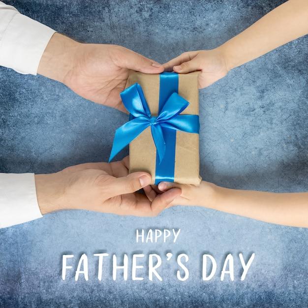 Szczęśliwy dzień ojcaprezent w rękach córki i ojca na niebieskim tle