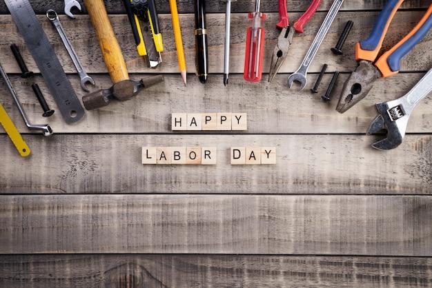 Szczęśliwy dzień pracy, drewniany blok kalendarza z wieloma przydatnymi narzędziami na drewnianym