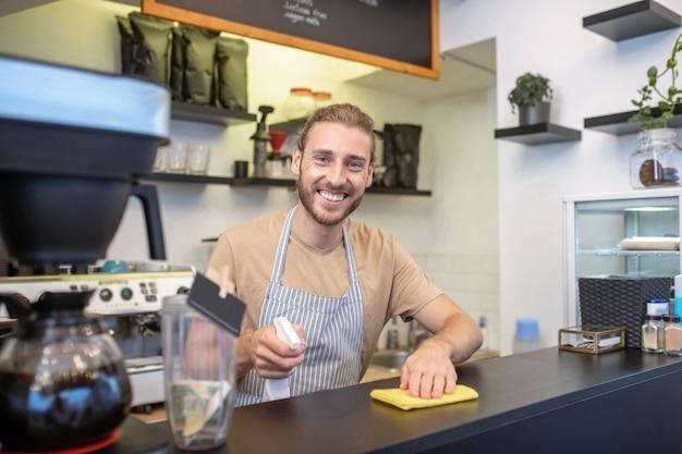 Szczęśliwy dzień. szczęśliwy uśmiechnięty młody brodaty mężczyzna w fartuch z serwetką i środkiem dezynfekującym stojący za kontuarem barowym