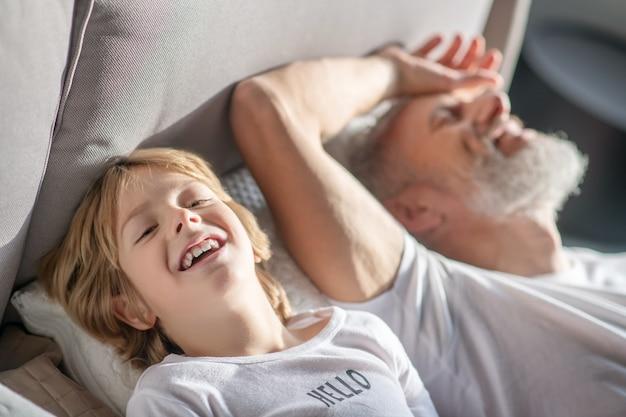 Szczęśliwy dzień. szczęśliwy wesoły dziecko i tata w domu ubrania, leżąc na łóżku, śmiejąc się
