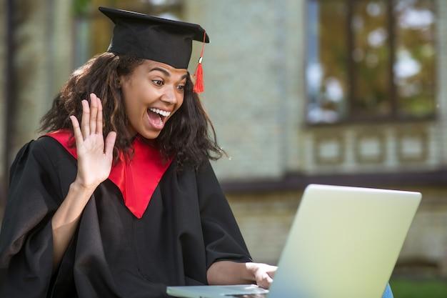 Szczęśliwy dzień. urocza absolwentka w akademickiej sukni, która ma rozmowę i czuje się szczęśliwa