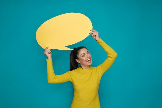 Szczęśliwy dziewczyny mienia koloru żółtego papieru mowy bąbla koszt stały.