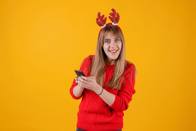 Szczęśliwy dziewczyny mienia smartphone w rękach jest ubranym śmiesznego boże narodzenie obręcz