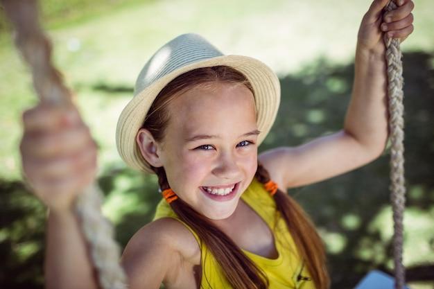 Szczęśliwy dziewczyny obsiadanie na huśtawce w parku