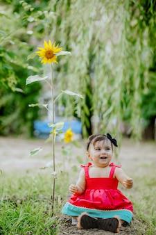 Szczęśliwy dziewięć miesięcy dziecko siedzi w ogrodzie obok słonecznika i uśmiecha się