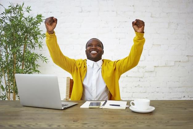 Szczęśliwy, ekstatyczny, młody, modny, ciemnoskóry biznesmen uśmiecha się podekscytowany i unosząc zaciśnięte pięści, radując się, świętując udane spotkanie, negocjacje, dobry interes, kontrakt lub zwycięstwo