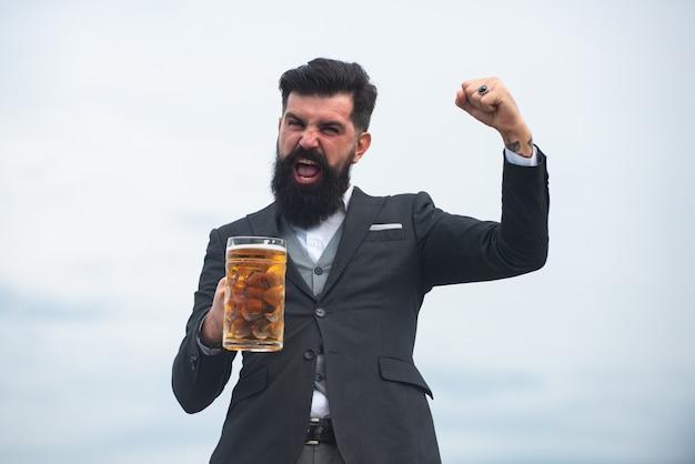 Szczęśliwy elegancki mężczyzna pije piwo. podekscytowany piwowar trzymający szklankę z piwem. wyrażanie emocji.