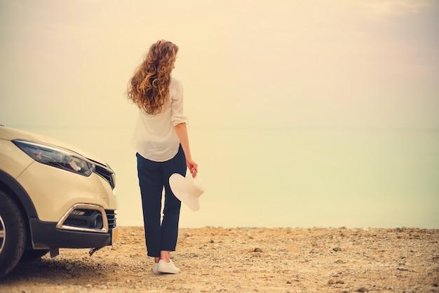 Szczęśliwy elegancki młoda kobieta podróżnik na plażowym drogowym obsiadaniu na białym skrzyżowaniu samochodu