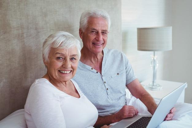 Szczęśliwy emerytowany pary mienia laptop