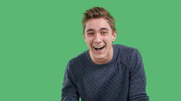 Szczęśliwy, emocjonalny młody człowiek śmieje się na zielonym, odizolowanym tle