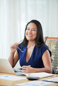 Szczęśliwy etniczny bizneswoman przy stołem w biurze
