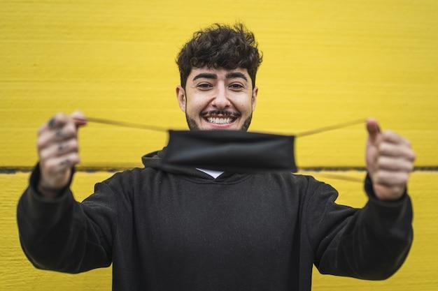 Szczęśliwy europejski mężczyzna pokazujący maskę na żywej żółtej ścianie