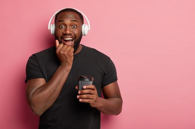 Szczęśliwy facet czuje się zrelaksowany podczas zwykłego porannego rytuału, słucha motywującej muzyki w słuchawkach, doskonale łączy kawę i piosenkę