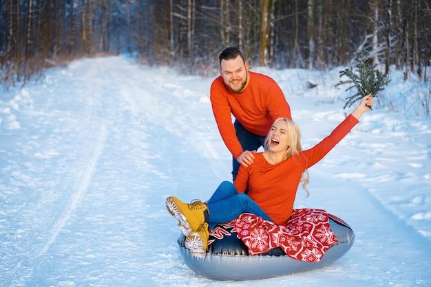 Szczęśliwy facet i dziewczyna jedzie w śniegu
