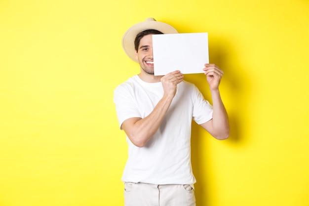 Szczęśliwy facet na wakacjach pokazuje pustą kartkę papieru na twoje logo, trzymając znak w pobliżu twarzy i uśmiechając się, stojąc na żółtym tle