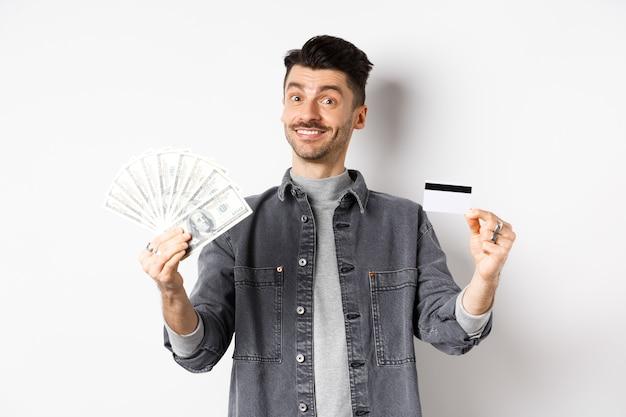 Szczęśliwy facet pokazuje plastikową kartę kredytową i dolary, dając wybór, stojąc na białym tle.
