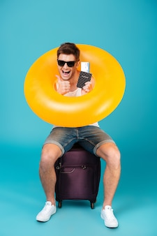 Szczęśliwy facet siedzi na walizce w okularach przeciwsłonecznych