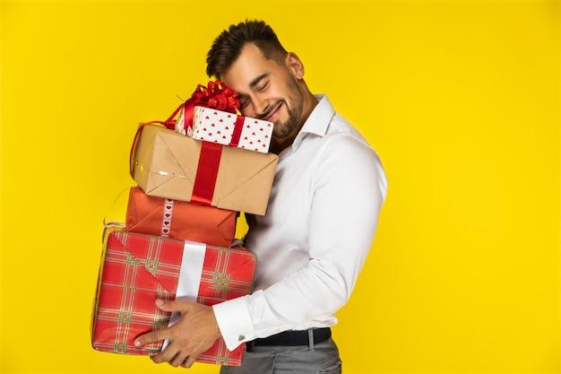 Szczęśliwy facet trzyma pudełka z prezentami