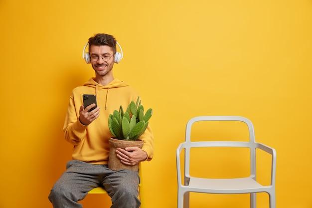 Szczęśliwy facet używa telefonu komórkowego, pobiera muzykę z listy odtwarzania, słucha ulubionej piosenki w słuchawkach, spędza wolny czas w domu w pozach przy pustym krześle