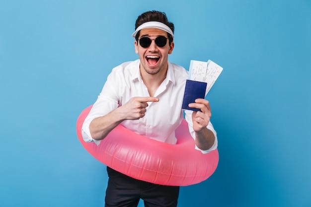 Szczęśliwy facet w białej koszuli i ciemnych spodniach pozuje z nadmuchiwanym kółkiem, dokumentami i biletami. portret mężczyzny w okularach i czapce na niebieskiej przestrzeni.