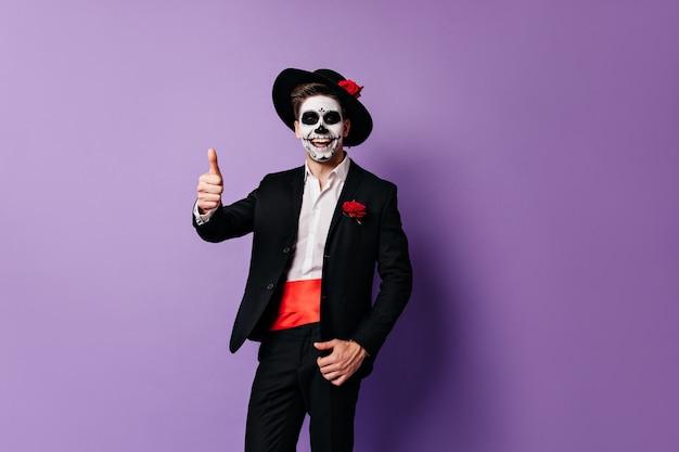 Szczęśliwy facet w meksykańskich strojach i masce śmieje się i pokazuje kciuk do góry na fioletowym tle.