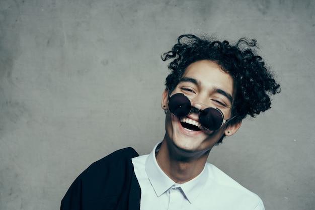 Szczęśliwy facet w okularach kręcone włosy model uśmiech nastolatka