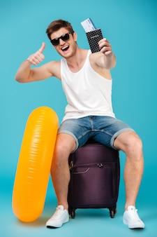 Szczęśliwy facet w okularach przeciwsłonecznych siedzi na torbie koloru