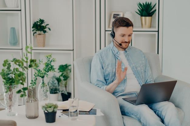 Szczęśliwy facet w zestawie słuchawkowym macha ręką na kamerę internetową laptopa, siedząc na krześle w domu i rozmawiając online z przyjacielem, uśmiechnięty mężczyzna freelancer rozmawiający z kolegami podczas zdalnej pracy