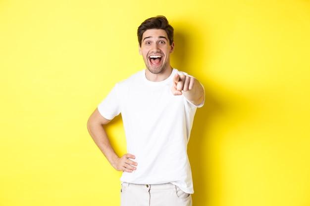 Szczęśliwy facet wskazując palcem na aparat i śmiejąc się, sprawdź coś, stojąc na żółtym tle.