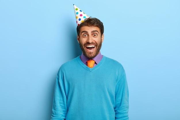 Szczęśliwy facet z kapeluszem urodziny pozowanie w niebieskim swetrze