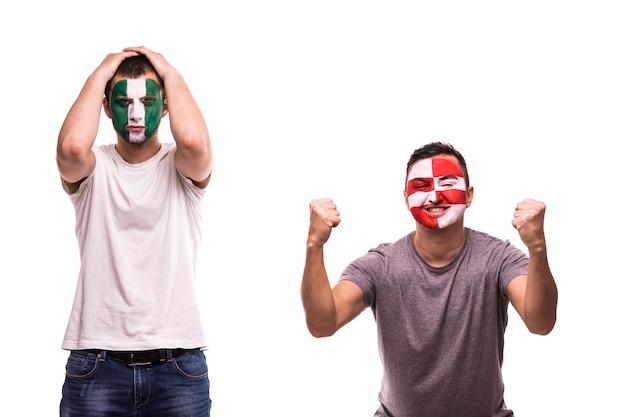 Szczęśliwy fan piłki nożnej z chorwacji świętuje zwycięstwo nad zdenerwowanym kibicem nigerii z pomalowaną twarzą