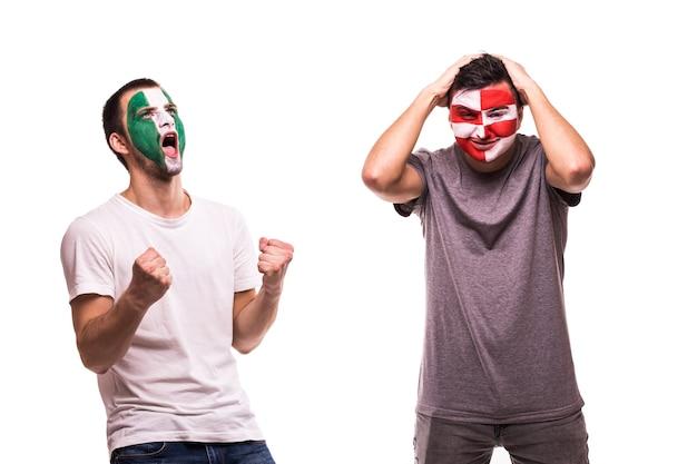 Szczęśliwy fan piłki nożnej z nigerii świętuje zwycięstwo nad zdenerwowanym kibicem chorwacji z pomalowaną twarzą