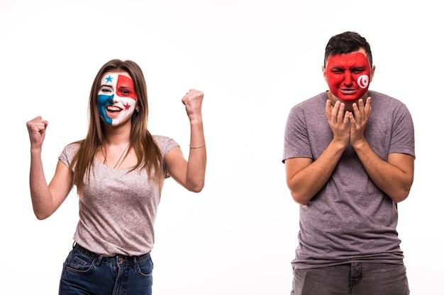 Szczęśliwy fan piłki nożnej z panamy świętuje zwycięstwo nad zdenerwowanym kibicem tunezji z pomalowaną twarzą na białym tle