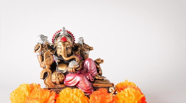 Szczęśliwy festiwal ganeśćaturthi, brązowy posąg ganeśy i złota tekstura z kwiatami, ganesh jest hinduskim bogiem sukcesu.