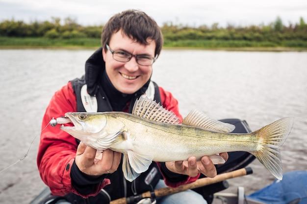 Szczęśliwy fisher z szczupakową żerdzią patrzeje kamerę