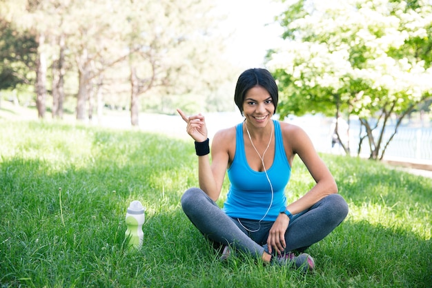 Szczęśliwy fitness kobieta siedzi na zielonej trawie