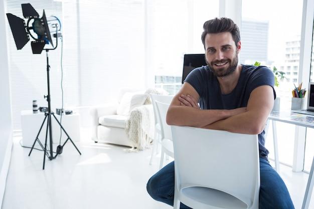 Szczęśliwy fotograf mężczyzna siedzi w studio