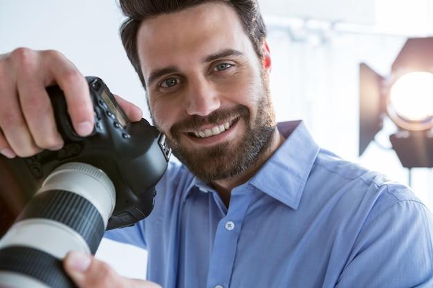 Szczęśliwy fotograf mężczyzna stojący w studio