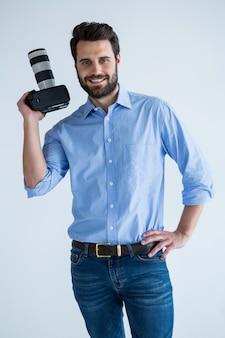 Szczęśliwy fotograf trzymając aparat w studio