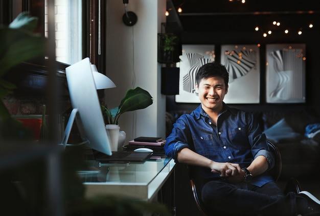 Szczęśliwy freelancer siedzący przy swoim biurku komputerowym w domu