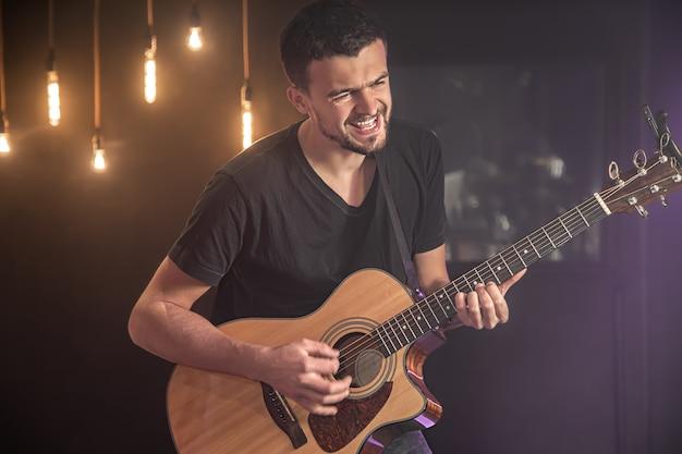 Szczęśliwy gitarzysta w czarnej koszulce gra na gitarze akustycznej na koncercie na niewyraźnym czarnym tle.