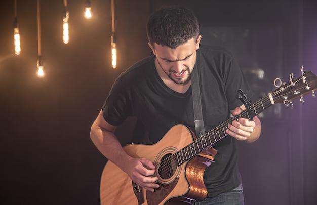 Szczęśliwy gitarzysta w czarnej koszulce gra na gitarze akustycznej na koncercie pod niewyraźną czarną ścianą.