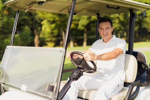 Szczęśliwy golfista w luksusowym wózku golfowym człowiek ma odpoczynek.