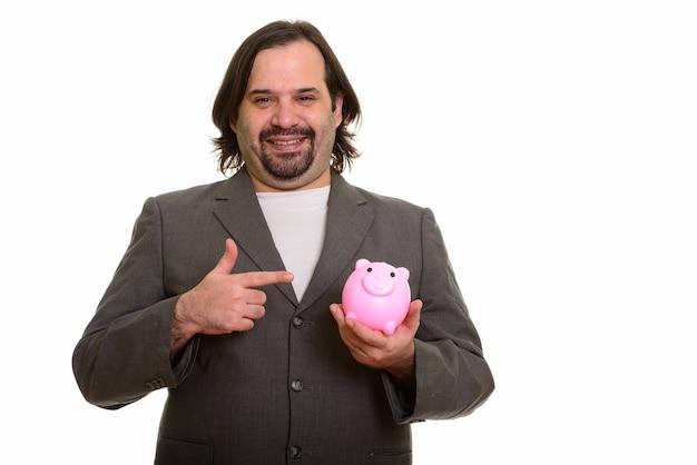 Szczęśliwy gruby biznesmen kaukaski uśmiechając się i trzymając skarbonkę, wskazując palcem