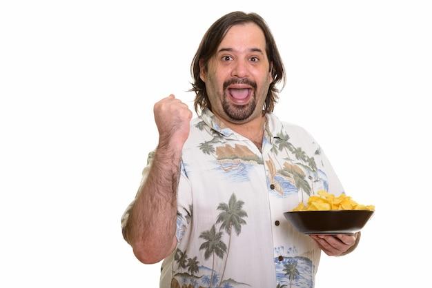 Szczęśliwy gruby kaukaski mężczyzna uśmiecha się i szuka zmotywowany, trzymając miskę frytek