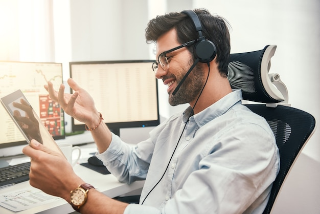 Szczęśliwy handlowiec odnoszący sukcesy brodaty biznesmen w zestawie słuchawkowym, trzymając cyfrowy tablet rozmawiający z klientem